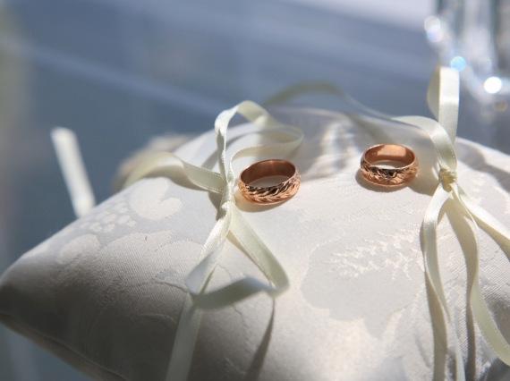 白いリボンが付いたリングピローに金の結婚指輪が置かれている
