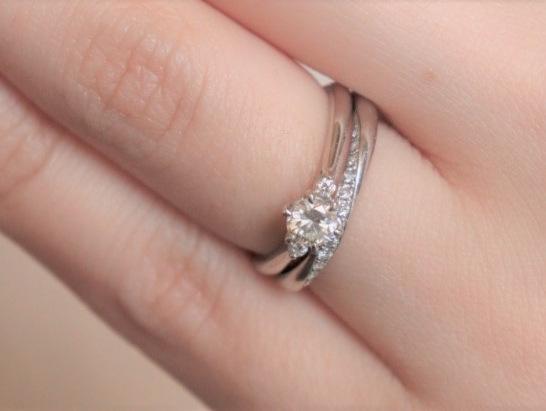 プラチナの結婚指輪と婚約指輪を重ねづけしている画像