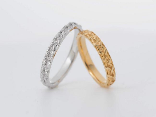 レースのような模様が入ったプラチナと金の結婚指輪