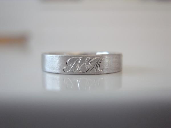 平打ちにイニシャルが手彫りされた結婚指輪
