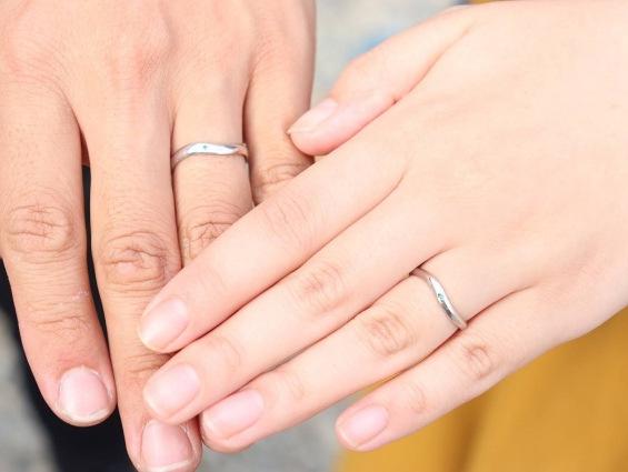 プラチナの結婚指輪をしたカップルの手